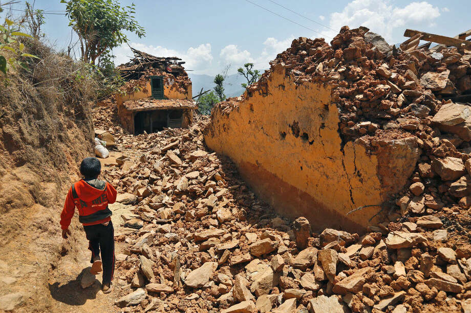 A Nepalese boy runs past houses destroyed by last week's earthquake in Pauwathok village, Sindhupalchok district, Nepal, Saturday, May 2, 2015. Life has been slowly returning to normal in Kathmandu, but to the east, angry villagers in parts of the Sindhupalchok district said Saturday they were still waiting for aid to reach them. In the village of Pauwathok, where all but a handful of the 85 houses were destroyed, three trucks apparently carrying aid supplies roared by without stopping. (AP Photo/Manish Swarup)