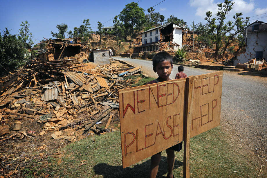 A Nepalese boy stands outside his village with a signboard asking for help in Pauwathok village, Sindhupalchok district, Nepal, Saturday, May 2, 2015. Life has been slowly returning to normal in Kathmandu, but to the east, angry villagers in parts of the Sindhupalchok district said Saturday they were still waiting for aid to reach them. In the village of Pauwathok, where all but a handful of the 85 houses were destroyed, three trucks apparently carrying aid supplies roared by without stopping. (AP Photo / Manish Swarup)