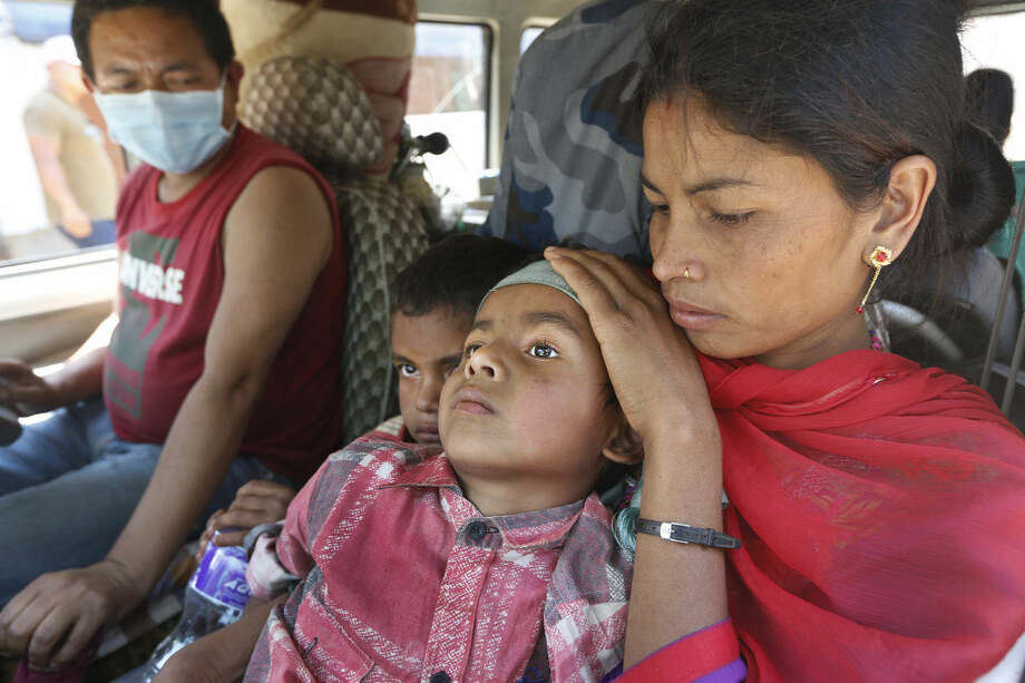 A Nepalese mother takes her injured son to a hospital in an ambulance in Chautara, Sindhupalchok district, Nepal, Saturday, May 2, 2015. Life has been slowly returning to normal in Kathmandu, but to the east, angry villagers in parts of the Sindhupalchok district said Saturday they were still waiting for aid to reach them. (AP Photo / Manish Swarup)