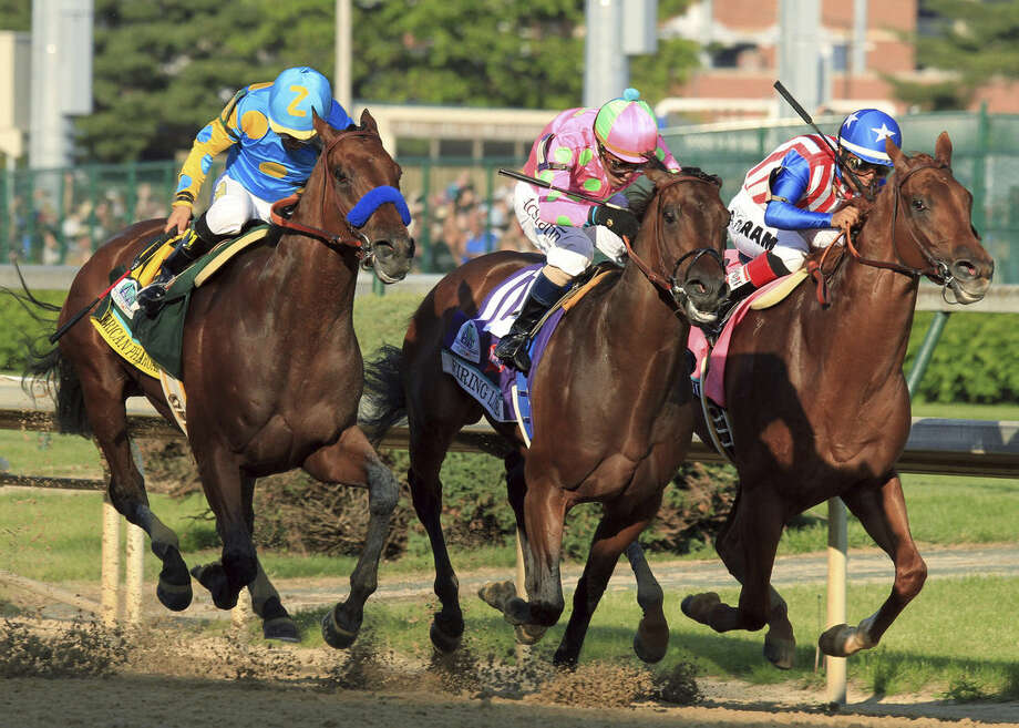 Victor Espinoza, left, rides American Pharoah to victory in the 141st running of the Kentucky Derby horse race at Churchill Downs Saturday, May 2, 2015, in Louisville, Ky. (AP Photo/Garry Jones)