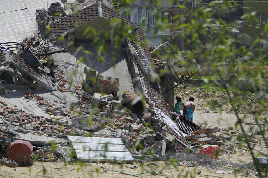 A Nepalese woman bathes with the help of her friend outside a house damaged in the earthquake in Kathmandu, Nepal, Saturday, May 2, 2015. A week after the devastating earthquake, life is limping back to normal in Nepal. (AP Photo/Niranjan Shrestha)