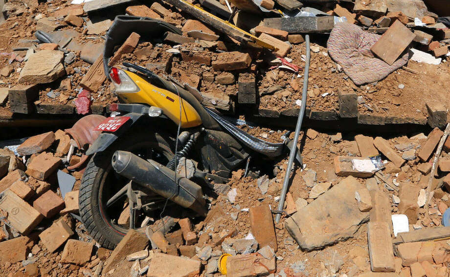 The back of a motorcycle sticks out from the debris of a house that collapsed from last week's earthquake in Chautara, Sindhupalchok district, Nepal, Saturday, May 2, 2015. Life has been slowly returning to normal in Kathmandu, but to the east, angry villagers in parts of the Sindhupalchok district said Saturday they were still waiting for aid to reach them. (AP Photo / Manish Swarup)