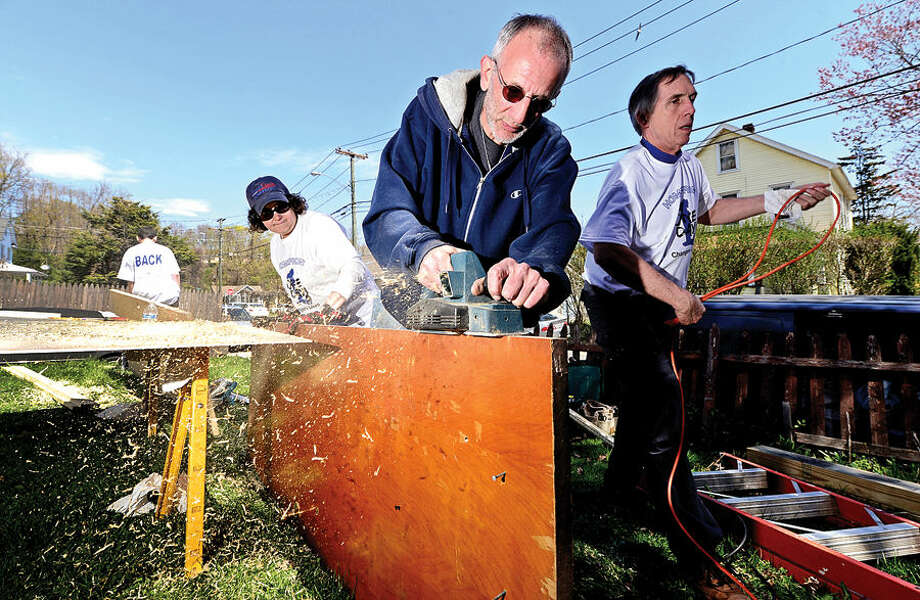 Hour photo / Erik Trautmann Homefront volunteer and Our Lady of Fatima parishioner, Tony Ruggi, planes a door at the 29 Oxford St. in Norwalk Saturday. Homefront is a community-based, volunteer-driven home repair program provides free repairs to low-income homeowners and non profits.