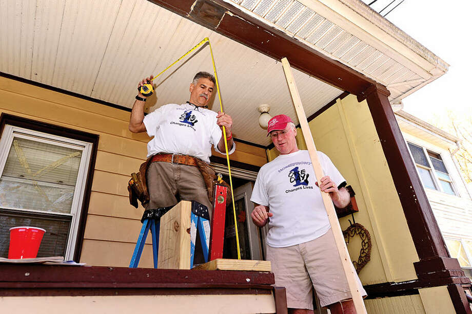 Hour photo / Erik Trautmann Homefront volunteer and Our Lady of Fatima parishioner, James Iannatti and John Danaher, fix the porch at the 29 Oxford St. in Norwalk Saturday. Homefront is a community-based, volunteer-driven home repair program provides free repairs to low-income homeowners and non profits.