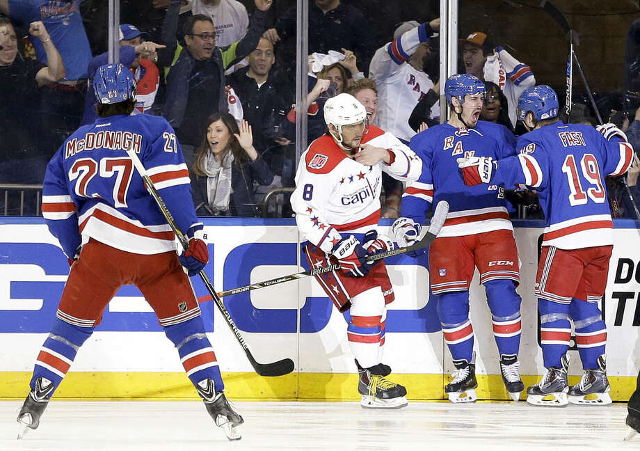 New York Rangers left wing Chris Kreider, second from right, and right wing Jesper Fast (19) celebrate Kreider's goal as the Washington Capitals Alex Ovechkin (8) skates past during the first period of Game 2 in the second round of the NHL Stanley Cup hockey playoffs Saturday, May 2, 2015, in New York. (AP Photo/Frank Franklin II)