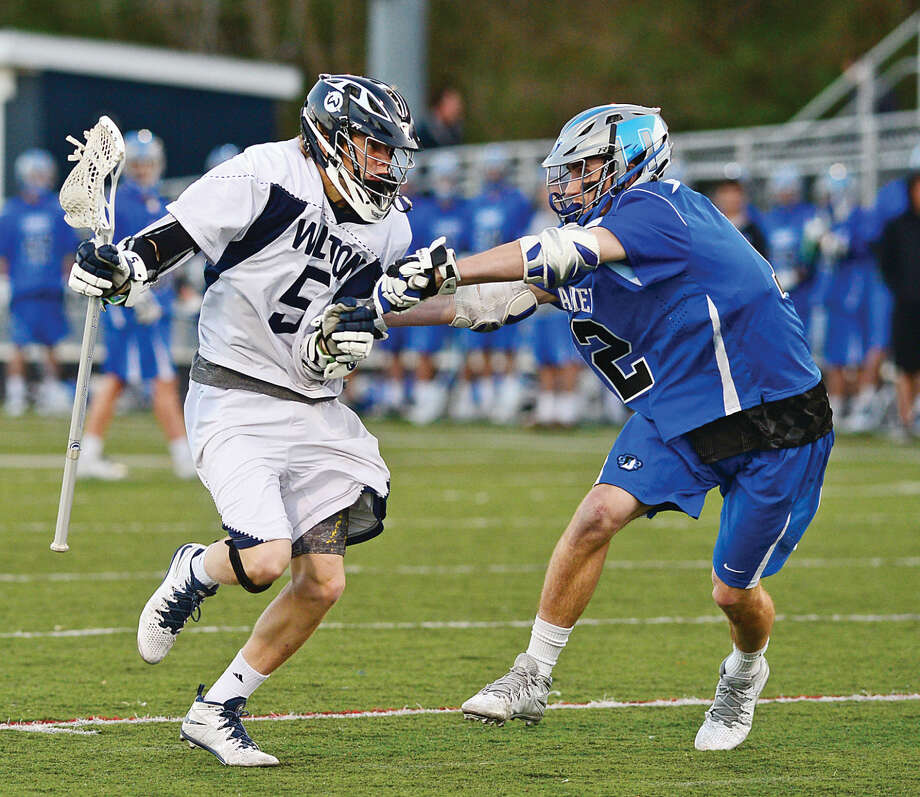 Hour photo / Erik Trautmann Wilton High School's Harrison Bardwell battles against Darien's William Hamernick during their game at Fujitani Field Saturday