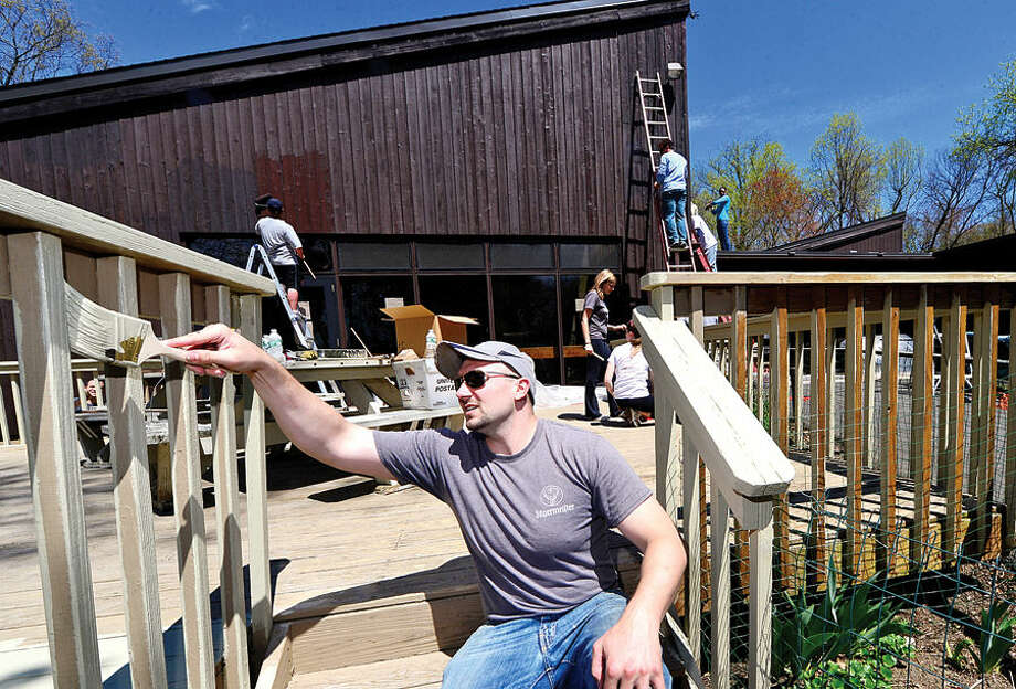 Hour photo / Erik Trautmann Homefront volunteer and Factset employee William Bunn paints the deck at the STAR facility on Wolfpit Ave in Norwalk Saturday. Homefront is a community-based, volunteer-driven home repair program provides free repairs to low-income homeowners and non profits.