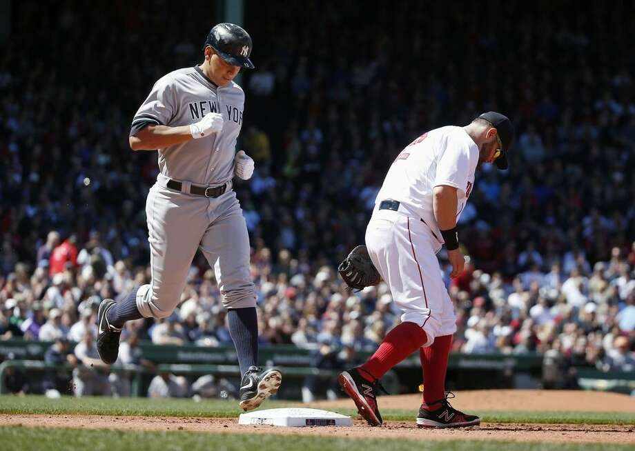 New York Yankees' Alex Rodriguez, left, touches first base behind Boston Red Sox's Mike Napoli on a ground out during the third inning of a baseball game in Boston, Saturday, May 2, 2015. (AP Photo/Michael Dwyer)