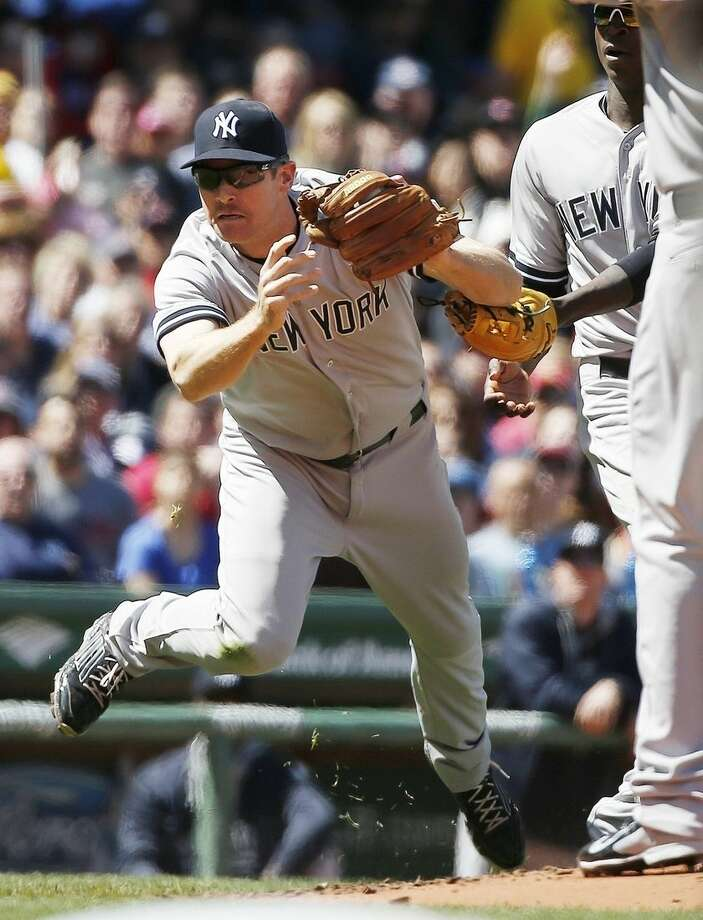 New York Yankees' Chase Headley stumbles after making the catch on a pop out by Boston Red Sox's Pablo Sandoval during the second inning of a baseball game in Boston, Saturday, May 2, 2015. (AP Photo/Michael Dwyer)
