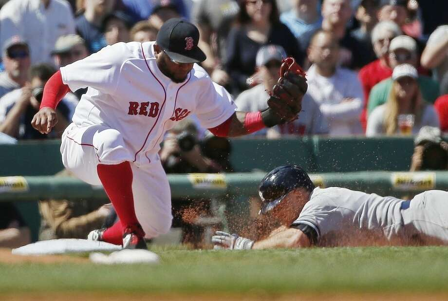 Boston Red Sox's Pablo Sandoval, left, puts the tag on New York Yankees' Brett Gardner, who is out at third base trying to reach on a double, during the third inning of a baseball game in Boston, Saturday, May 2, 2015. (AP Photo/Michael Dwyer)