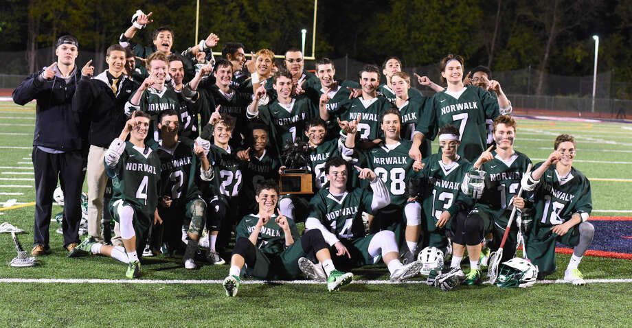 The Norwalk boys lacrosse teams poses with The Randy McCue Trophy after beating cross-city rival Brien McMahon 5-0 on Thursday at Casagrande Field.