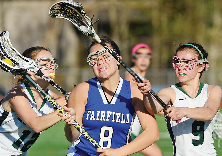 Hour photo / Erik Trautmann Norwalk's Emma Larchevesque, left, and Grace Bradley, battle against Fairfield Ludlowe's Cammy Hummelstone in their game Saturday at Testa field.