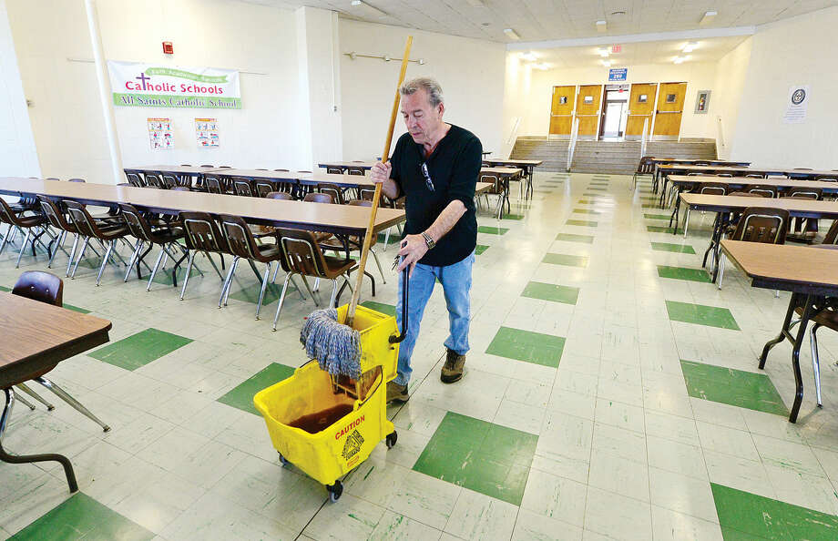 Al Martins performs his duties as a custodian at All Saint's Catholic School Wednesday in Norwalk, Conn. on April 27, 2016. Martin will be honored at the school's Golf Tournament and fundraiser on May 23rd.