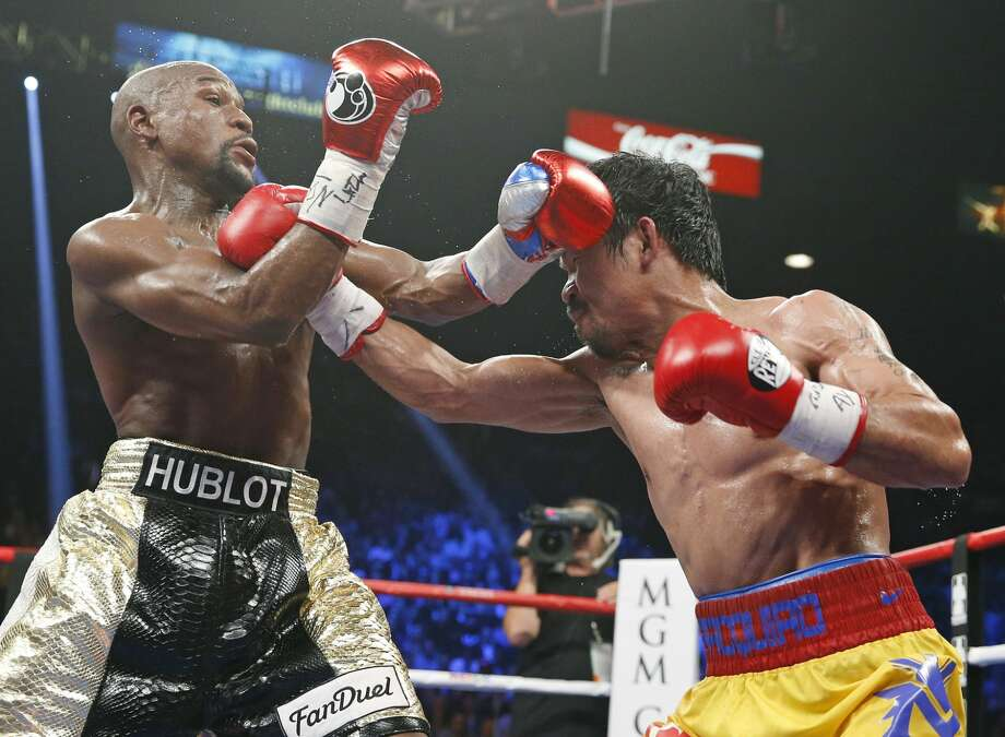 Manny Pacquiao, from the Philippines, right, connects with a right to the head of Floyd Mayweather Jr., during their welterweight title fight on Saturday, May 2, 2015 in Las Vegas. (AP Photo/John Locher)