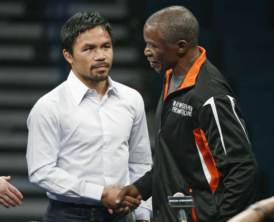 Manny Pacquiao, left, shakes hands with Floyd Mayweather Jr. during a press conference following their welterweight title fight on Saturday, May 2, 2015 in Las Vegas. Mayweather defeated Pacquiao in a unanimous decision. (AP Photo/John Locher)
