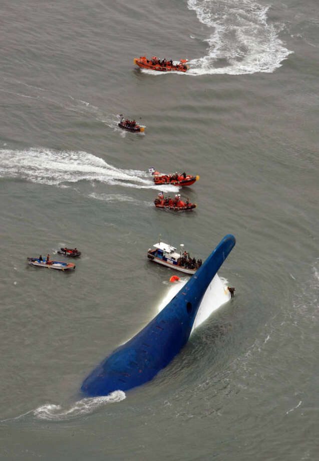 In this photo released by Jeollanamdo via Yonhap News Agency, South Korean rescue team boats and fishing boats try to rescue passengers of a ferry sinking off South Korea's southern coast, in the water off the southern coast near Jindo, south of Seoul, Wednesday, April 16, 2014. Nearly 300 people were still missing Wednesday several hours after a ferry carrying 477, most of them high school students, sank in cold waters off South Korea's southern coast. (AP Photo/Jeollanamdo via Yonhap) KOREA OUT