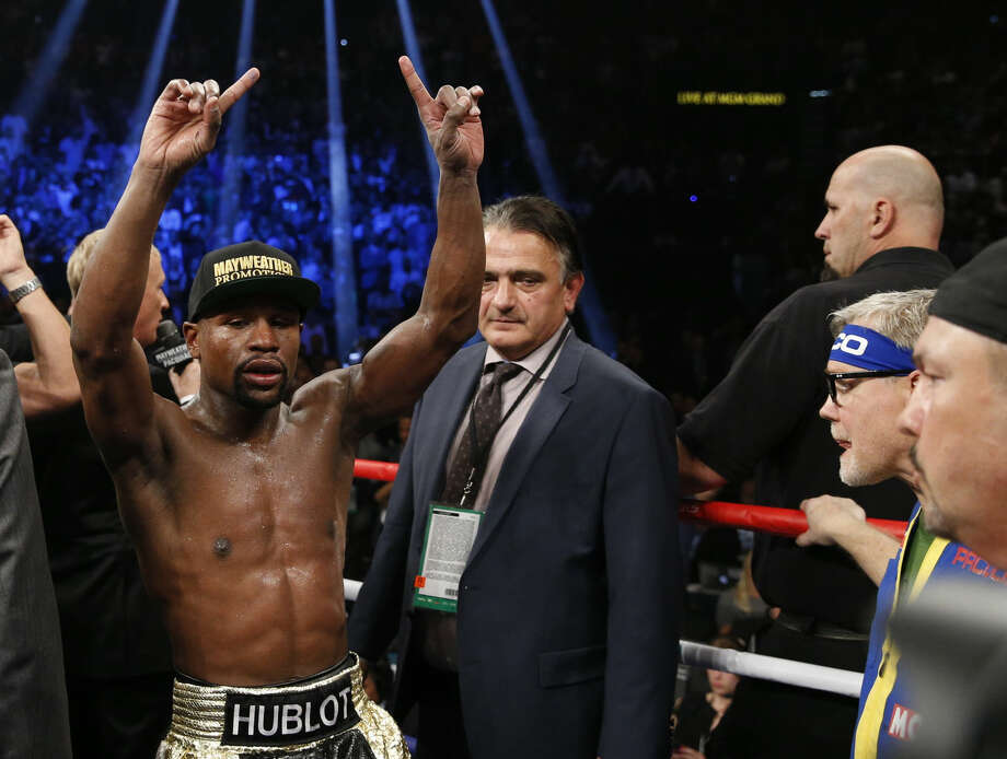 Floyd Mayweather Jr., left, celebrates after his welterweight title fight against Manny Pacquiao, from the Philippines, on Saturday, May 2, 2015 in Las Vegas. (AP Photo/John Locher)