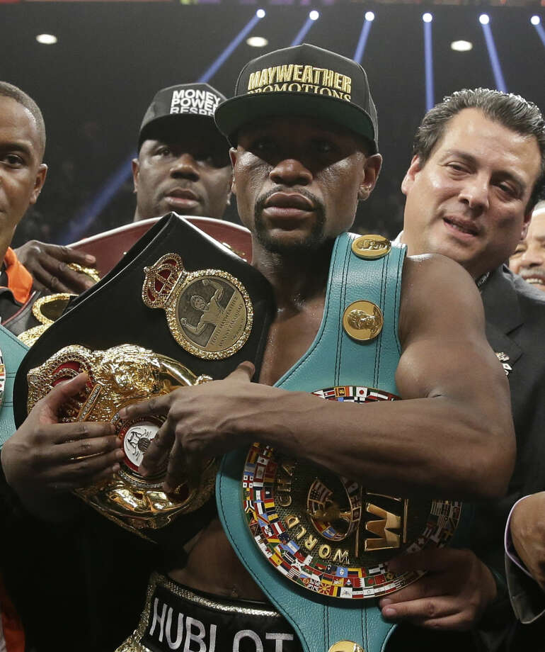 Floyd Mayweather Jr. carries the winner's belts after he defeated Manny Pacquiao, from the Philippines, in their welterweight title fight on Saturday, May 2, 2015 in Las Vegas. (AP Photo/Isaac Brekken)