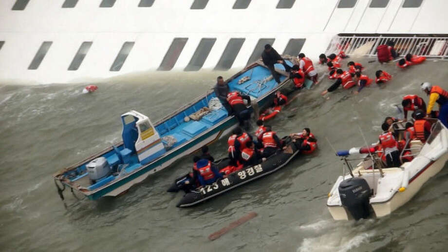 In this image taken from video from Mokpo Coast Guard, passengers from a ferry sinking off South Korea's southern coast, are rescued by South Korean Coast guard in the water off the southern coast near Jindo, south of Seoul, Wednesday, April 16, 2014. Nearly 300 people were still missing Wednesday several hours after the ferry carrying 477, most of them high school students, sank in cold waters off South Korea's southern coast. (AP Photo/Yonhap) KOREA OUT