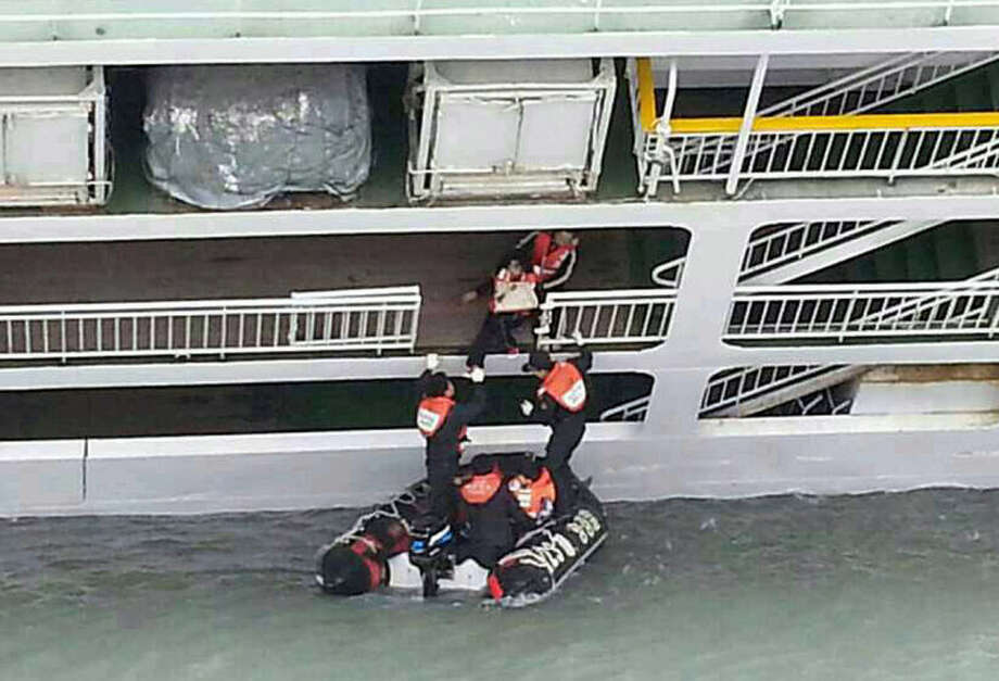 In this photo released by the South Korean Coast Guard via Yonhap News Agency, South Korean coast guard officers rescue passengers from a sinking ferry off the southern coast near Jindo, south of Seoul, South Korea, Wednesday, April 16, 2014. A ferry carrying 459 people, mostly high school students on an overnight trip to a tourist island, sank off South Korea's southern coast on Wednesday, leaving nearly 300 people missing despite a frantic, hours-long rescue by dozens of ships and helicopters. (AP Photo/South Korea Coast Guard via Yonhap) KOREA OUT