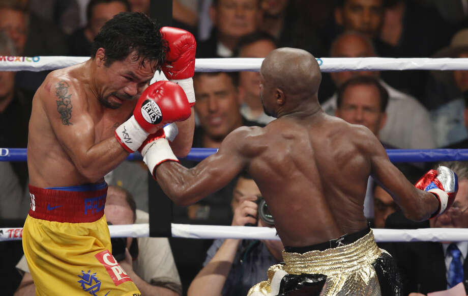 Floyd Mayweather Jr., right, hits Manny Pacquiao, from the Philippines, during their welterweight title fight on Saturday, May 2, 2015 in Las Vegas. (AP Photo/Eric Jamison)