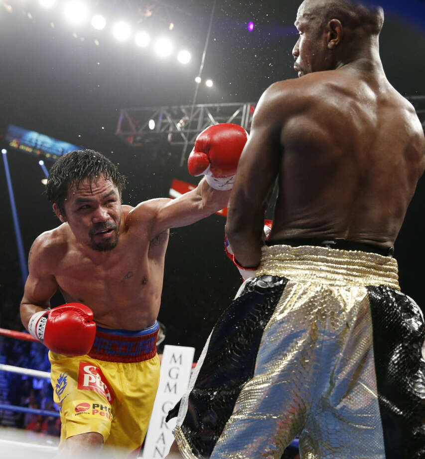 Manny Pacquiao, from the Philippines, left, punches Floyd Mayweather Jr., during their welterweight title fight on Saturday, May 2, 2015 in Las Vegas. (AP Photo/John Locher)