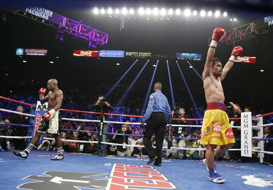 Floyd Mayweather Jr., left, and Manny Pacquiao, right, from the Philippines, return to their corners at the end of their welterweight title fight on Saturday, May 2, 2015 in Las Vegas. At center is referee Kenny Bayless. (AP Photo/John Locher)