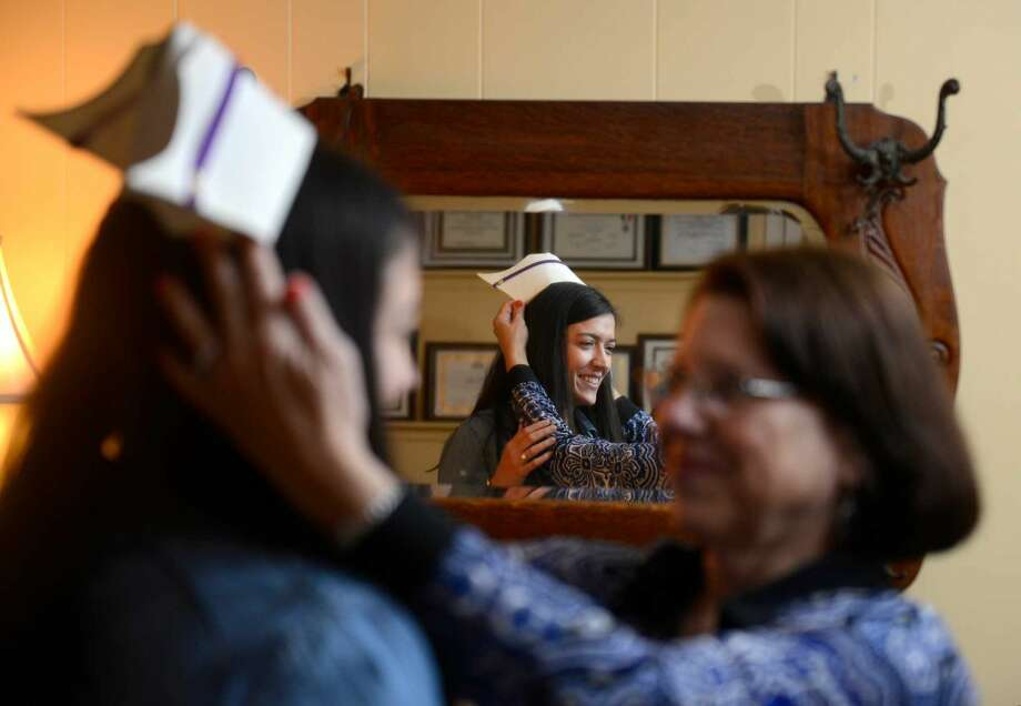 Kelly Olson tries on her mother, Lorraine nursing cap in the family room of their North Stamford home on April 26, 2016. Olson, 26, will fulfill her girlhood dream of becoming a nurse, like her mother, when she graduates from University of Bridgeport nursing school on Monday.