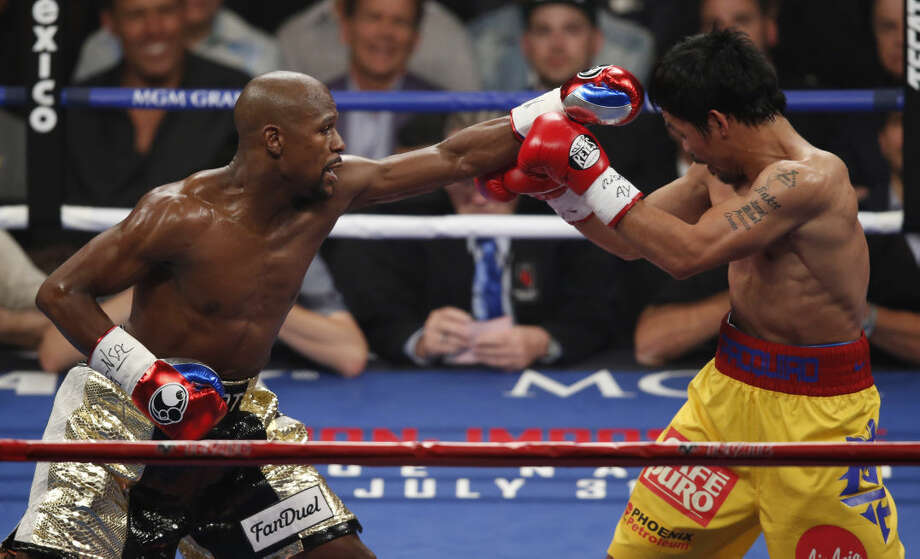 Manny Pacquiao, from the Philippines, right, blocks a shot by Floyd Mayweather Jr., during their welterweight title fight on Saturday, May 2, 2015 in Las Vegas. (AP Photo/Eric Jamison)