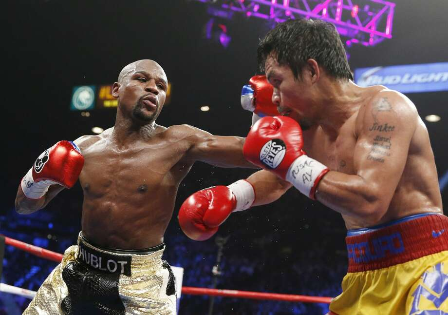 Floyd Mayweather Jr., left, lands a left against Manny Pacquiao, from the Philippines, during their welterweight title fight on Saturday, May 2, 2015 in Las Vegas. (AP Photo/John Locher)