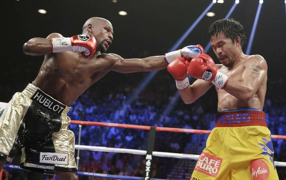 Floyd Mayweather Jr., left, stops Manny Pacquiao, from the Philippines, with a left during their welterweight title fight on Saturday, May 2, 2015 in Las Vegas. (AP Photo/Isaac Brekken)