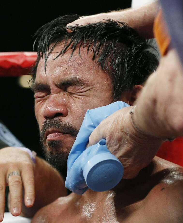 Manny Pacquiao, from the Philippines, is helped in his corner between rounds during his welterweight title fight against Floyd Mayweather Jr. on Saturday, May 2, 2015 in Las Vegas. (AP Photo/Isaac Brekken)