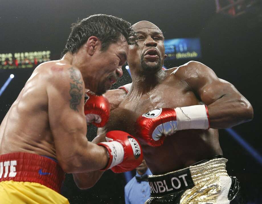 Manny Pacquiao, from the Philippines, left, and Floyd Mayweather Jr., trade blows during their welterweight title fight on Saturday, May 2, 2015 in Las Vegas. (AP Photo/John Locher)