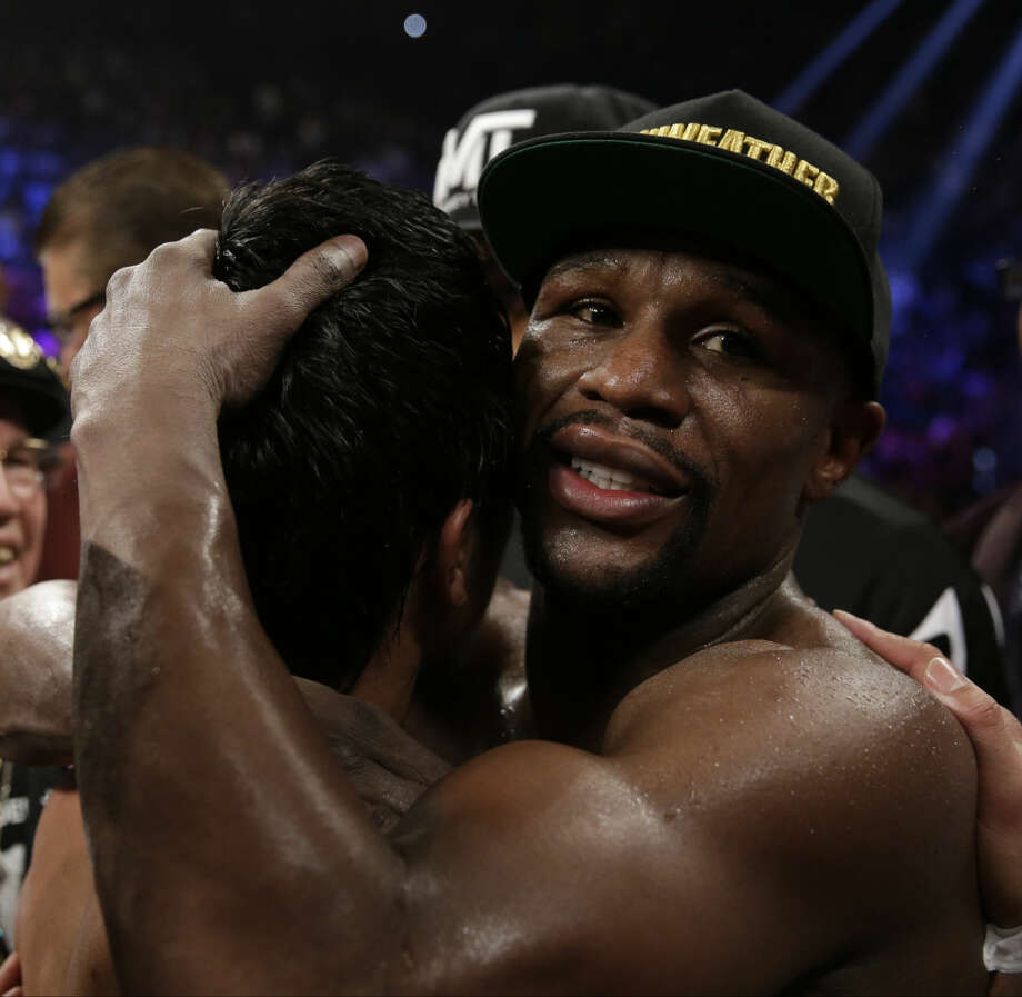 Floyd Mayweather Jr., right, hugs Manny Pacquiao, from the Philippines, after their welterweight title fight on Saturday, May 2, 2015 in Las Vegas. (AP Photo/Isaac Brekken)
