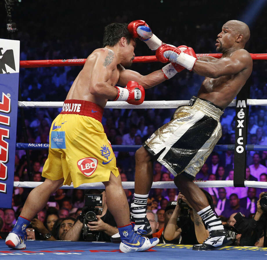 Manny Pacquiao, from the Philippines, left, trades blows with Floyd Mayweather Jr., during their welterweight title fight on Saturday, May 2, 2015 in Las Vegas. (AP Photo/John Locher)