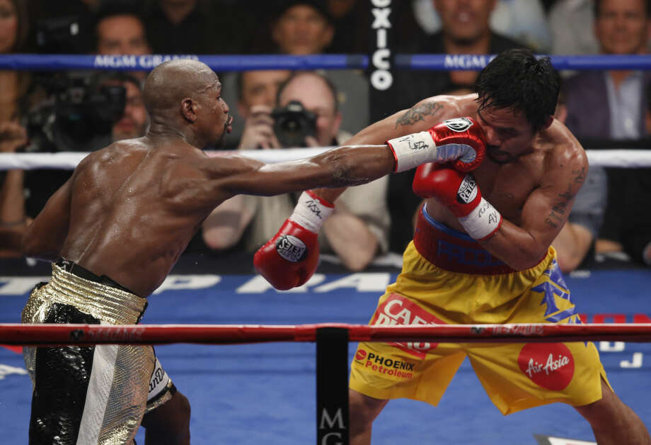 Floyd Mayweather Jr., left, hits Manny Pacquiao, from the Philippines, during their welterweight title fight on Saturday, May 2, 2015 in Las Vegas. (AP Photo/Eric Jamison)