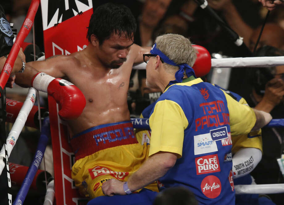 Manny Pacquiao, left, listens to trainer Freddie Roach between rounds of his welterweight title fight against Floyd Mayweather Jr. on Saturday, May 2, 2015 in Las Vegas. (AP Photo/Eric Jamison)
