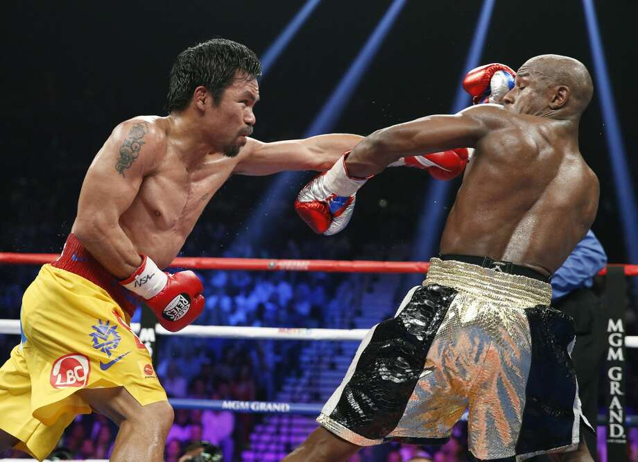 Floyd Mayweather Jr., right, pulls away from a punch thrown by Manny Pacquiao, from the Philippines, during their welterweight title fight on Saturday, May 2, 2015 in Las Vegas. (AP Photo/John Locher)
