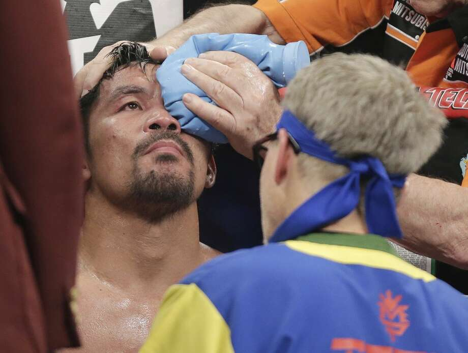 Manny Pacquiao, from the Philippines, is helped in his corner between rounds during his welterweight title fight against Floyd Mayweather Jr. on Saturday, May 2, 2015 in Las Vegas. At right is trainer Freddie Roach. (AP Photo/Isaac Brekken)
