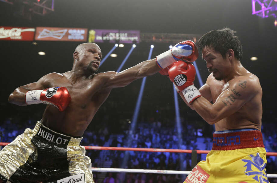 Floyd Mayweather Jr., left, trades blows with Manny Pacquiao, from the Philippines, during their welterweight title fight on Saturday, May 2, 2015 in Las Vegas. (AP Photo/Isaac Brekken)