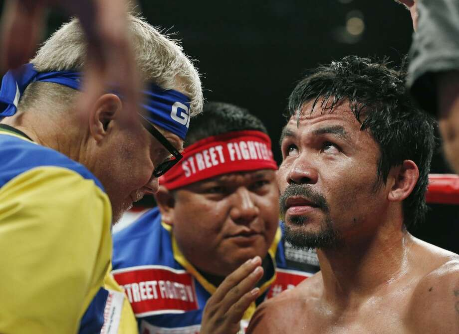 Manny Pacquiao, from the Philippines, right, listens to his trainer Freddie Roach, left, during their welterweight title fight on Saturday, May 2, 2015 in Las Vegas. (AP Photo/John Locher)