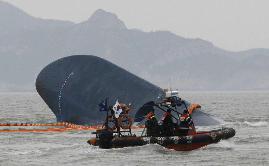 South Korean Coast Guard officers search for missing passengers from a sunken ferry in the water off the southern coast near Jindo, South Korea, Thursday, April 17, 2014. Strong currents, rain and bad visibility hampered an increasingly anxious search Thursday for more than 280 passengers still missing a day after their ferry flipped onto its side and sank in cold waters off the southern coast of South Korea.(AP Photo/Ahn Young-joon)