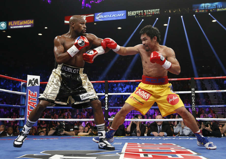 Manny Pacquiao, right, from the Philippines, trades blows with Floyd Mayweather Jr., during their welterweight title fight on Saturday, May 2, 2015 in Las Vegas. (AP Photo/John Locher)