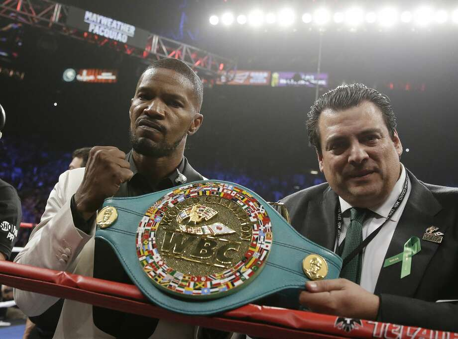 Actor Jamie Foxx, left, poses with the champion's belt after singing the national anthem before the start of the world welterweight championship bout between Floyd Mayweather Jr., and Manny Pacquiao, on Saturday, May 2, 2015 in Las Vegas.(AP Photo/Isaac Brekken)