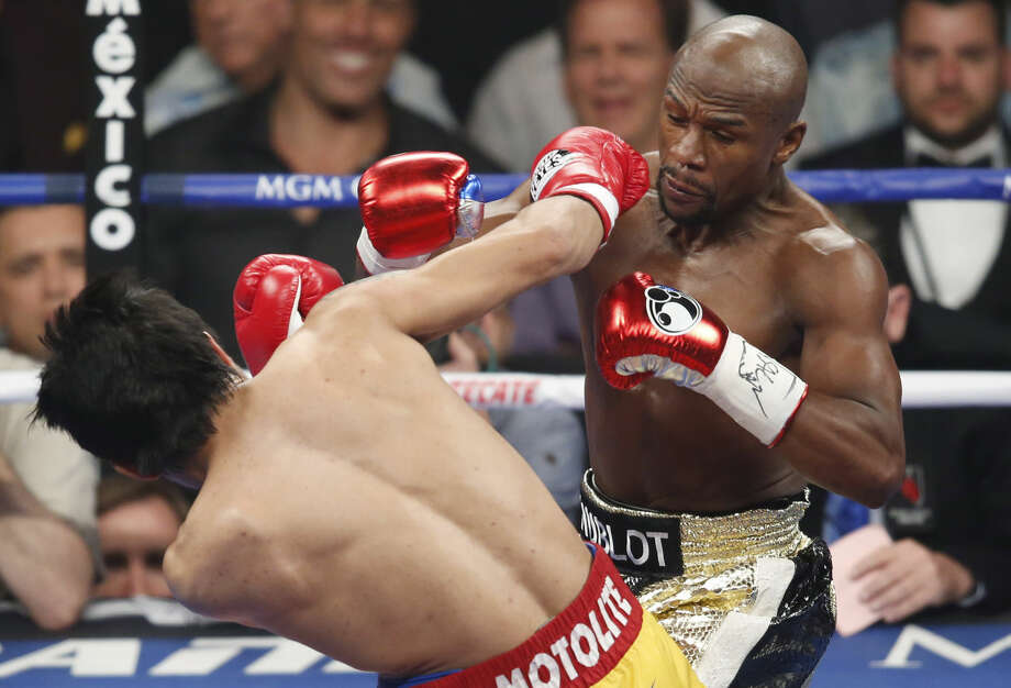 Manny Pacquiao, left, from the Philippines, throws a punch at Floyd Mayweather Jr., during their welterweight title fight on Saturday, May 2, 2015 in Las Vegas. (AP Photo/Eric Jamison)