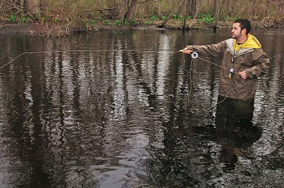 Thomas Lametta fishes on the Norwalk River in Wilton Saturday on the opening day of trout season. Hour photo / Erik Trautmann