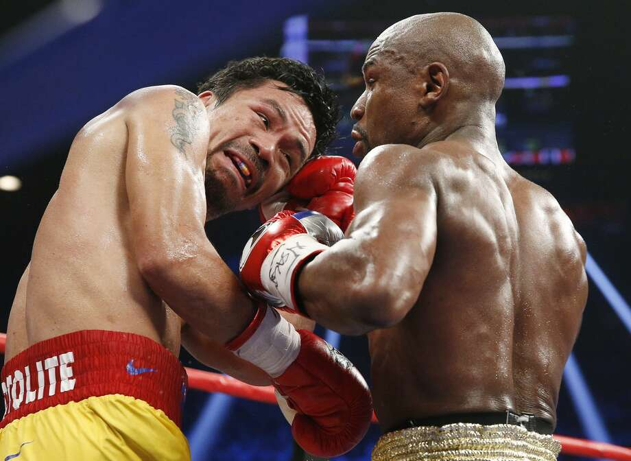 Manny Pacquiao, from the Philippines, left, trades punches with Floyd Mayweather Jr., during their welterweight title fight on Saturday, May 2, 2015 in Las Vegas. (AP Photo/John Locher)