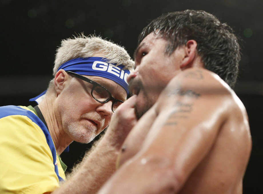 Trainer Freddie Roach, left, checks on Manny Pacquiao, from the Philippines, during their welterweight title fight against Floyd Mayweather Jr. on Saturday, May 2, 2015 in Las Vegas. (AP Photo/John Locher)
