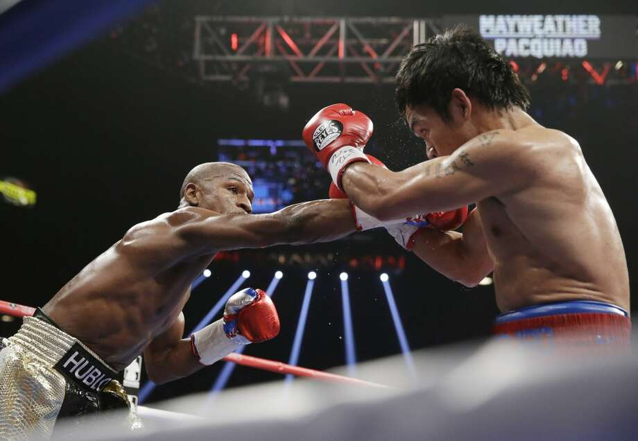 Floyd Mayweather Jr., left, drives Manny Pacquiao, from the Philippines, back with a right to the head during their welterweight title fight on Saturday, May 2, 2015 in Las Vegas. (AP Photo/Isaac Brekken)