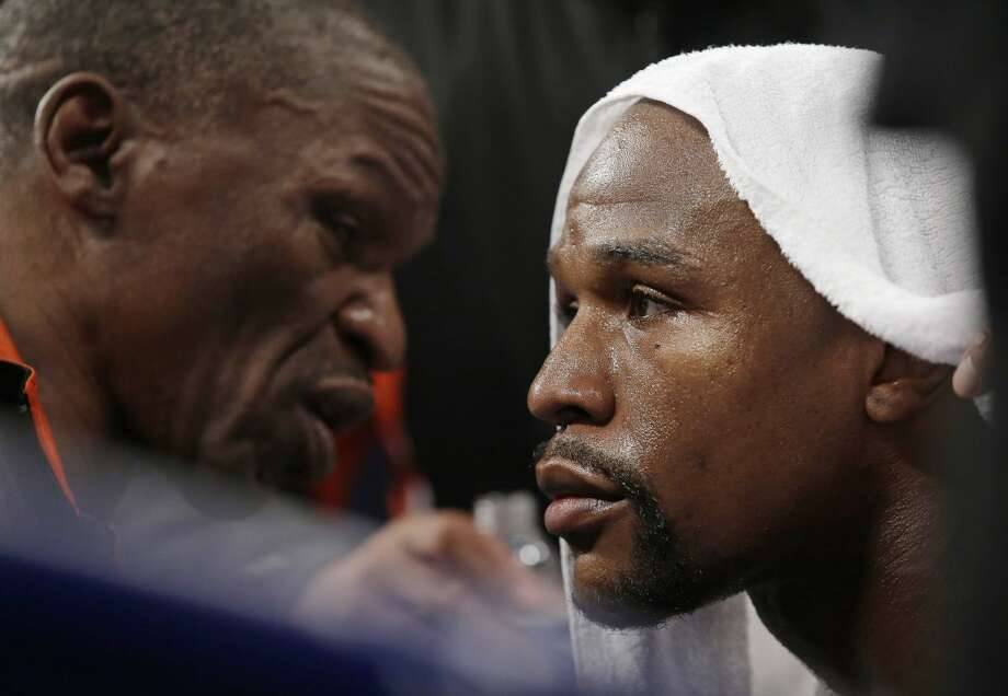 Floyd Mayweather Jr., right, listens to his father, head trainer Floyd Mayweather Sr., between rounds during his welterweight title fight against Manny Pacquiao, from the Philippines, on Saturday, May 2, 2015 in Las Vegas. (AP Photo/Isaac Brekken)